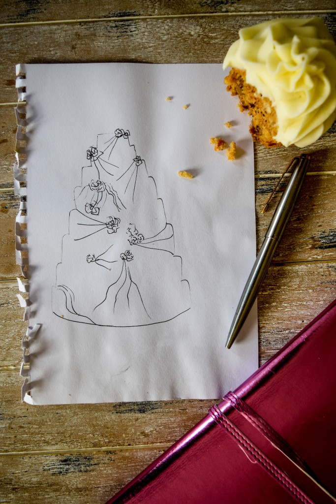 a piece of paper with a a sketch of a wedding cake with a half eaten cupcake, a silver oen and a pink note book on the righthand side