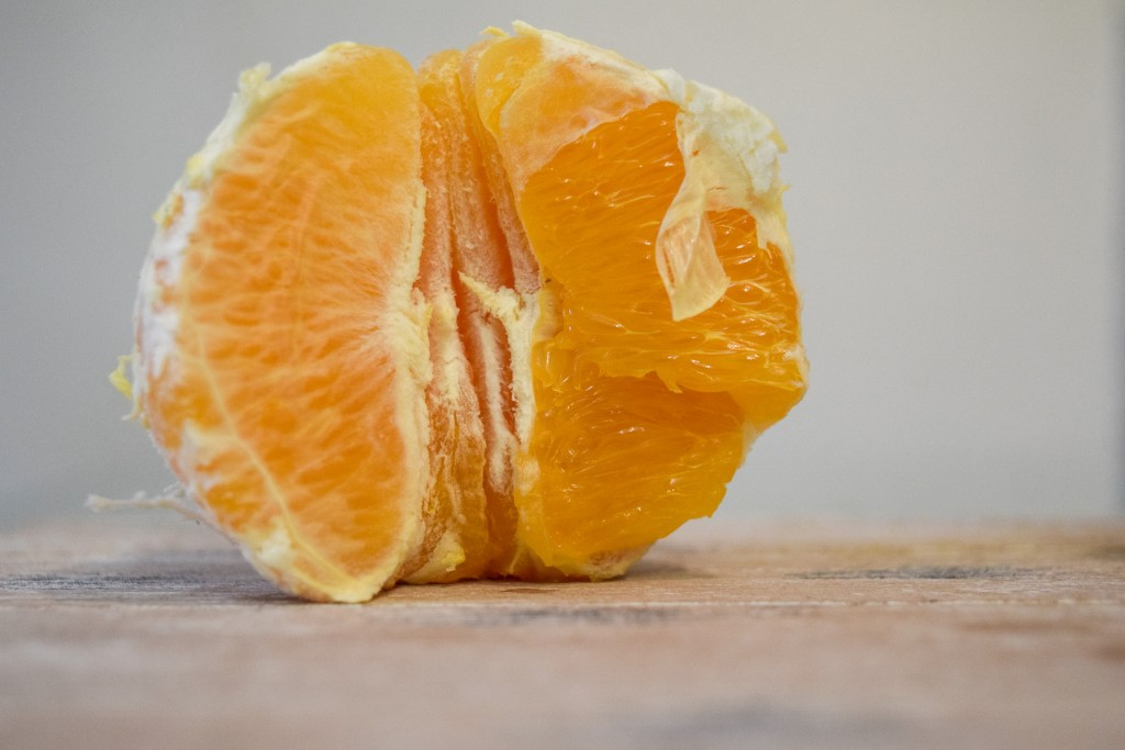 half a peeled orange with segments still attached