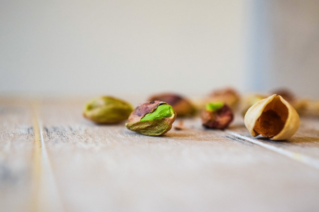 a green pistachio and an open pistachio shell in focus with 4 pistachio nuts in the background not in focused on a pale white washed wooden plank