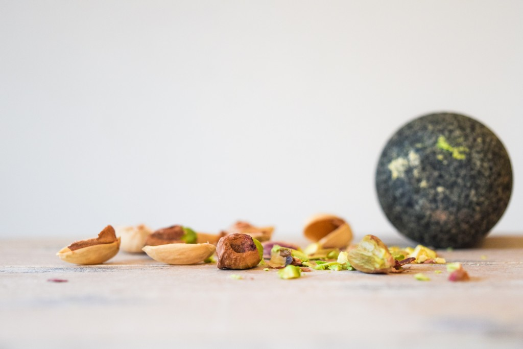 a pile of whole pistachios, crushed pistachios and pistachio shells and the circular base of a dark navy granite pestle in the background