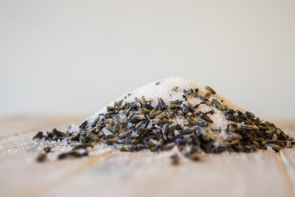 a pile on lavender grains and caster sugar on a pale white washed wooden plank