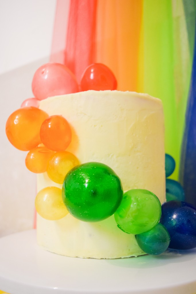 a white coloured cake with rainbow coloured spheres cascading down the sides and a rainbow background