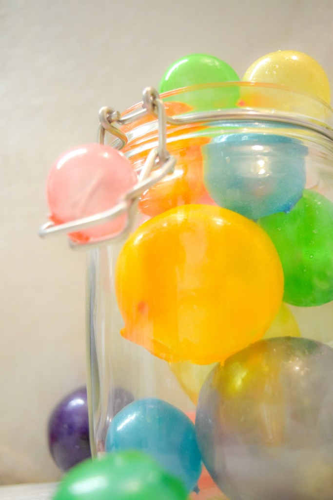 rainbow gelatin bubbles, balls, spheres in an open glass jar coloured red, orange, yellow, green, blue and purple on a white background