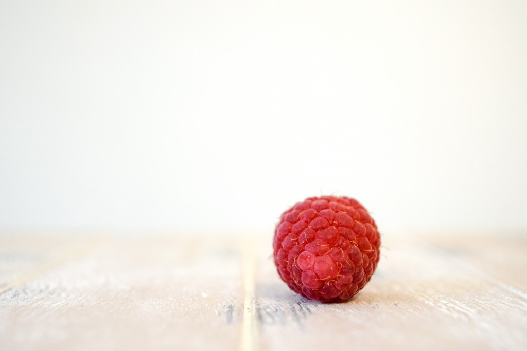 a red raspberry on its back showing the base of the raspberry lying a a pale white washed wooden plank