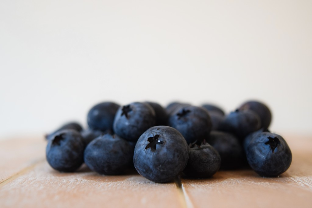 a pile of blueberries on cream planked wood
