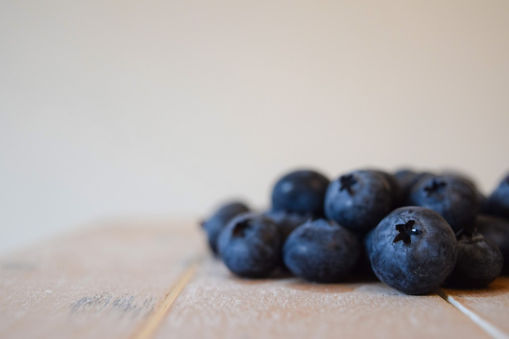 a pile of blueberries on the righthand side on a pale white washed wooden plank