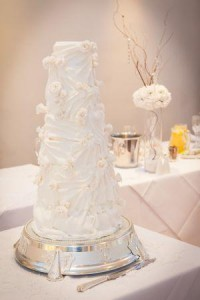 ggmix 8 tiered white wedding cake covered with white fondant roses and fondant pleats on a silver cake stand base