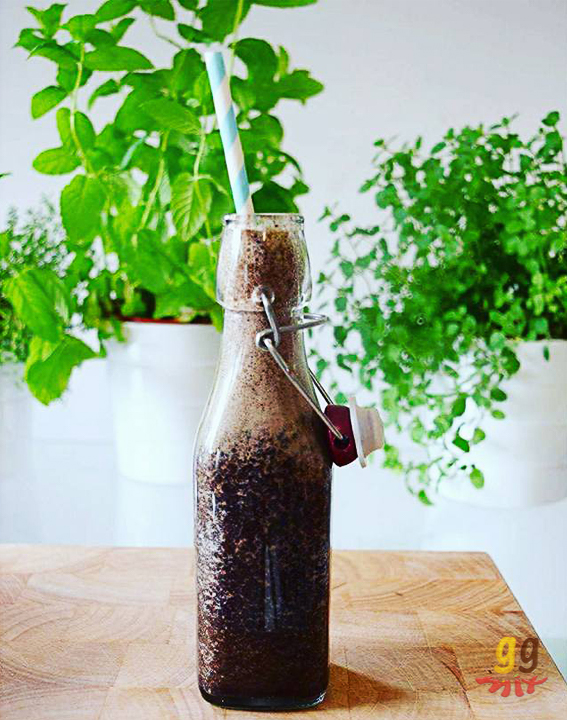Healthy blueberry, banana, spinach and cinnamon green smoothie drink in a glass bottle with a striped blue and white straw and herbs in the background ggmix