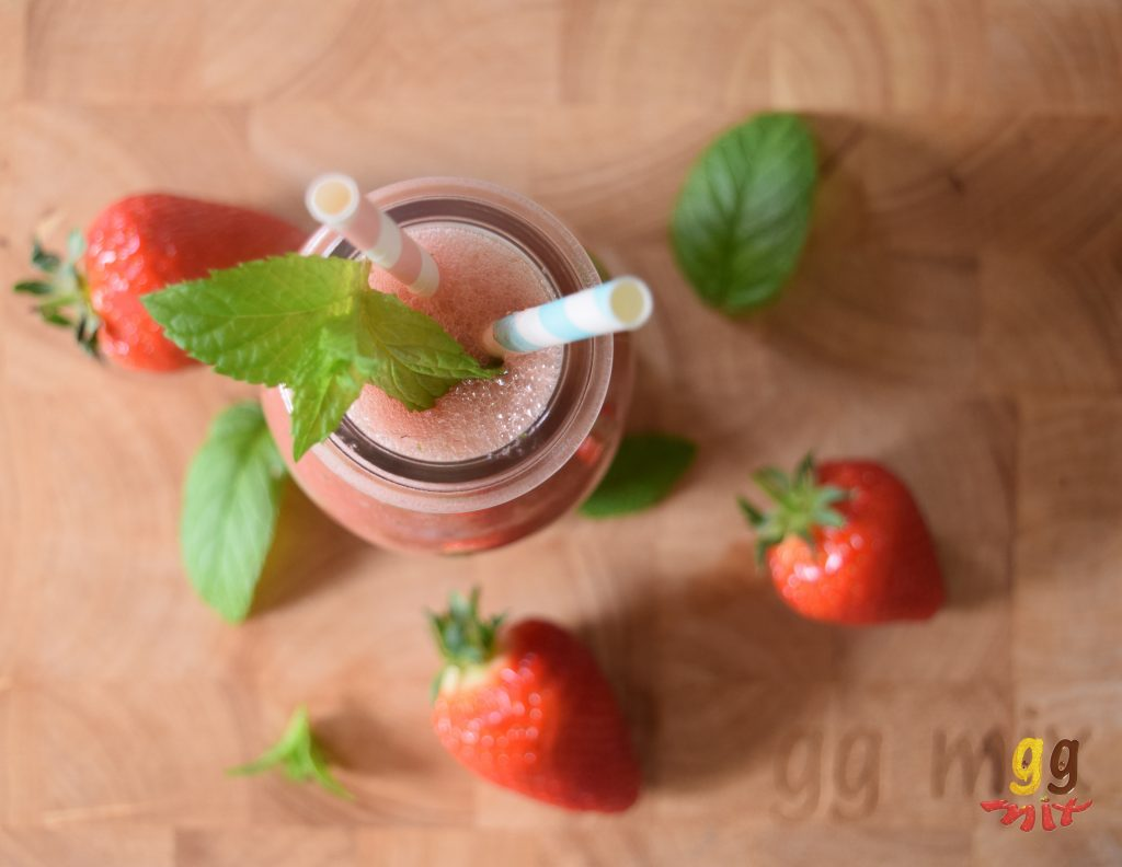 Healthy watermelon, strawberry, mint and rose smoothie drink with fresh mint leaves on the top of the smoothie. Mint leaves and 3 strawberries are sprinkled around the smoothie and a pink and white and a blue and white straw are in the smoothie ggmix