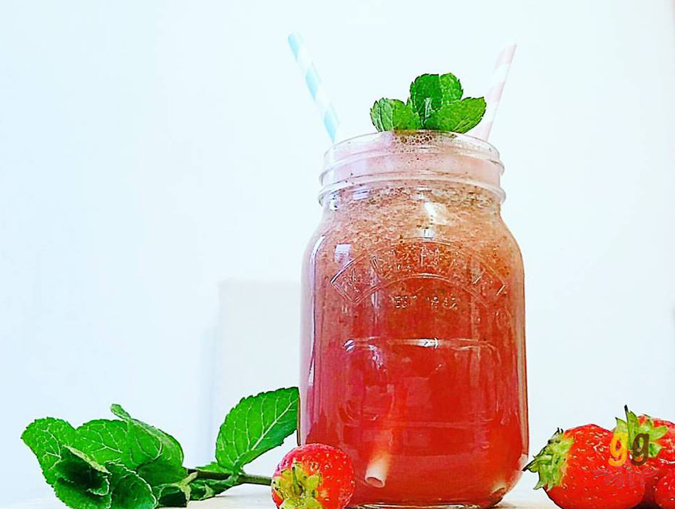 Healthy watermelon, strawberry, mint and rose smoothie drink in a glass jar with sprigs of mint on top and also by its side. Strawberries are also on the other side of the smoothie and a blue and white striped straw and a pink and white straw are in the smoothie ggmix