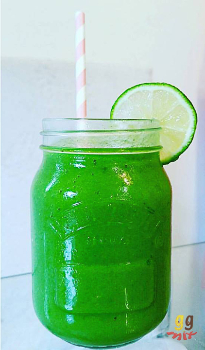 Healthy mango, pineapple, banana, spinach and mint green smoothie drink in a jar with a lime slice on the top and a pink and white straw ggmix