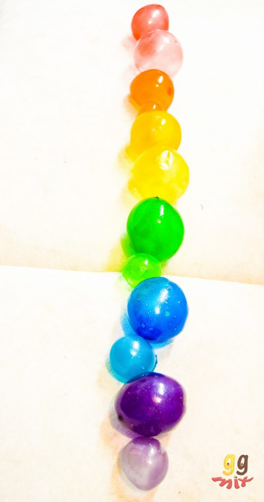 a row of rainbow gelatin bubbles coloured red, orange, yellow, green, blue and purple on a white background