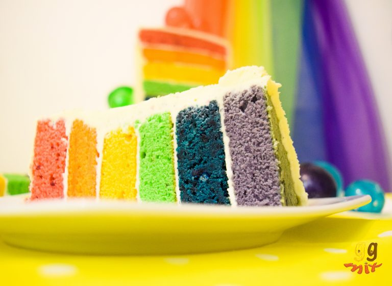a slice of rainbow cake with six layers coloured red,orange,yellow, green, blue and purple on a white plate and a yellow table