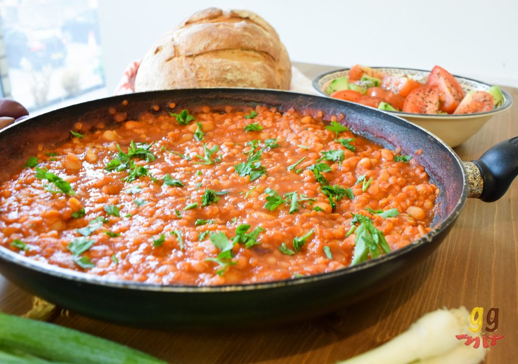 a pan of Greek fasolada posh beans on toast. Cannellini beans in a tomato sauce with parsley sprinkled on top. A bowl of chopped tomatoes and cucumbers sprinkled with dried mint. A round loaf of crusty bread on a white towel. A bowl of kalamata olives. A block of feta cheese sprinkled with dried oregano and a bunch of spring onions scallions. ggmix ggmixblog