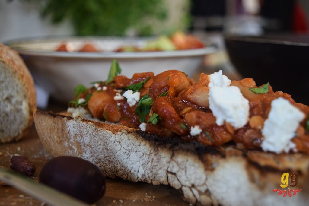 Greek fasolada fasolia posh beans on toast. Cannellini beans in a tomato sauce on a slice of crusty bread sprinkled with chopped parsley and feta. ggmix ggmix blog