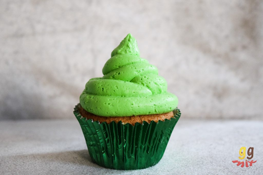 a cupecake in a metalic green cupcake case with lime green buttercream on the top