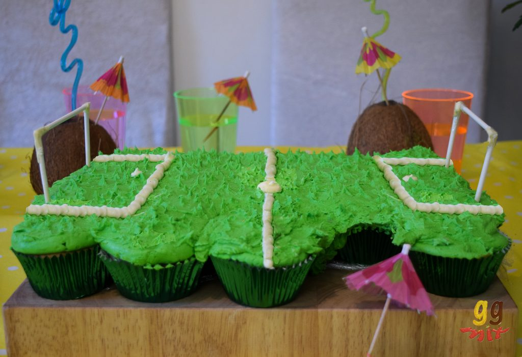 foot ball pitch made of cupcakes with green lime icing as the grass white buttercream for the pitch lines and goal posts made from cake pop sticks