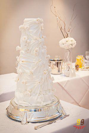 white 8 tiered wedding cake with white chocolate roses and fondant drapes
