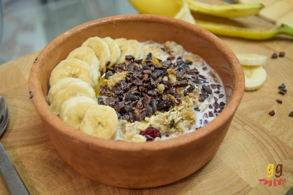 a bowl of granola topped with milk, sliced bananas and cacao nibs
