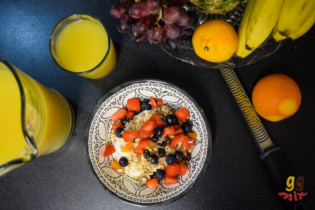 a bowl of granola, greek yogurt, strawberries bueberries and orange zest. There is a jug and glass of orange juice, a zester an orange and fruit around rhe granola