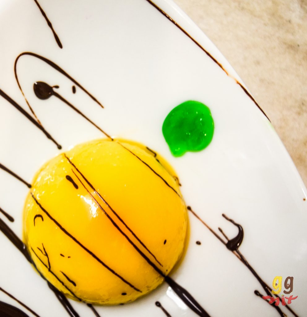 orange domed mini mirror glaze cake in the center of a bowl with dark chocolate drizzled over the top and a lime green sauce on the top left