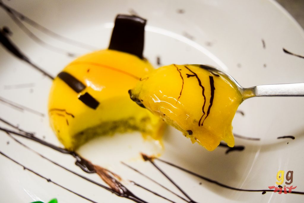 an orange domed mini mirror glaze cake dark chocolate drizzled over the top a piece of chocolate sticking out of the top right of the cake with a pice taken out and on a spoon