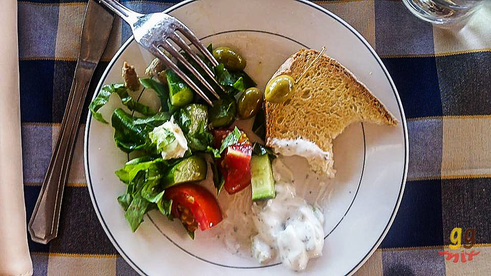 A PLATE OF GREEK SALAD, GREEN OLIVES, A BITTEN SLICE OF BREAD AND SOME TZATZAKI TALATOURI ON A BLUE AND WHITE HECKED TABLE CLOTH