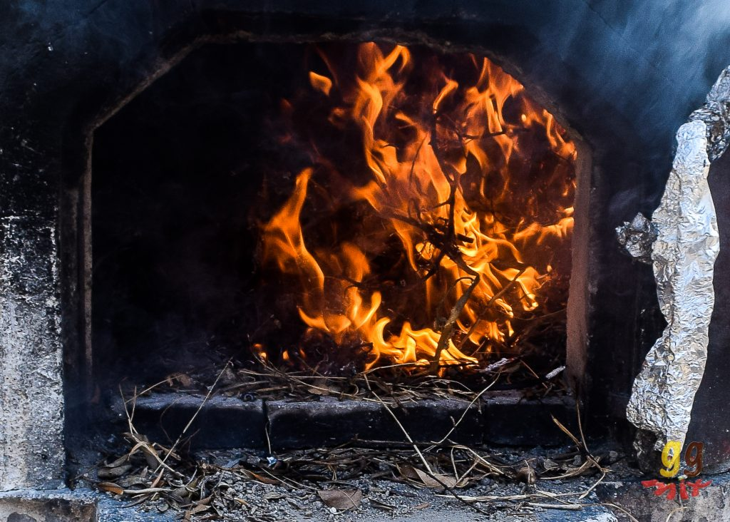 A CLOSE UP VIEW OF THE FLAMES INSIDE A TRADITIONAL GREEK VILLAGE CLAY OVEN THAT COOKS KLEFTIKO