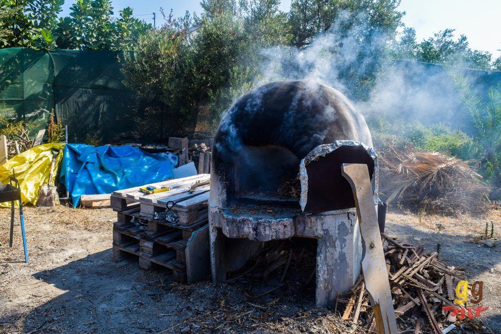 A TRADITIONAL CLAY KLEFTIKO OVEN WITH THE DOOR OPEN AND SMOKE COMING OUT OF IT