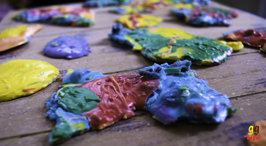 broken pieces of rainbow chocolate coloured in an abstract way with red, orange, yellow, green, blue and purple