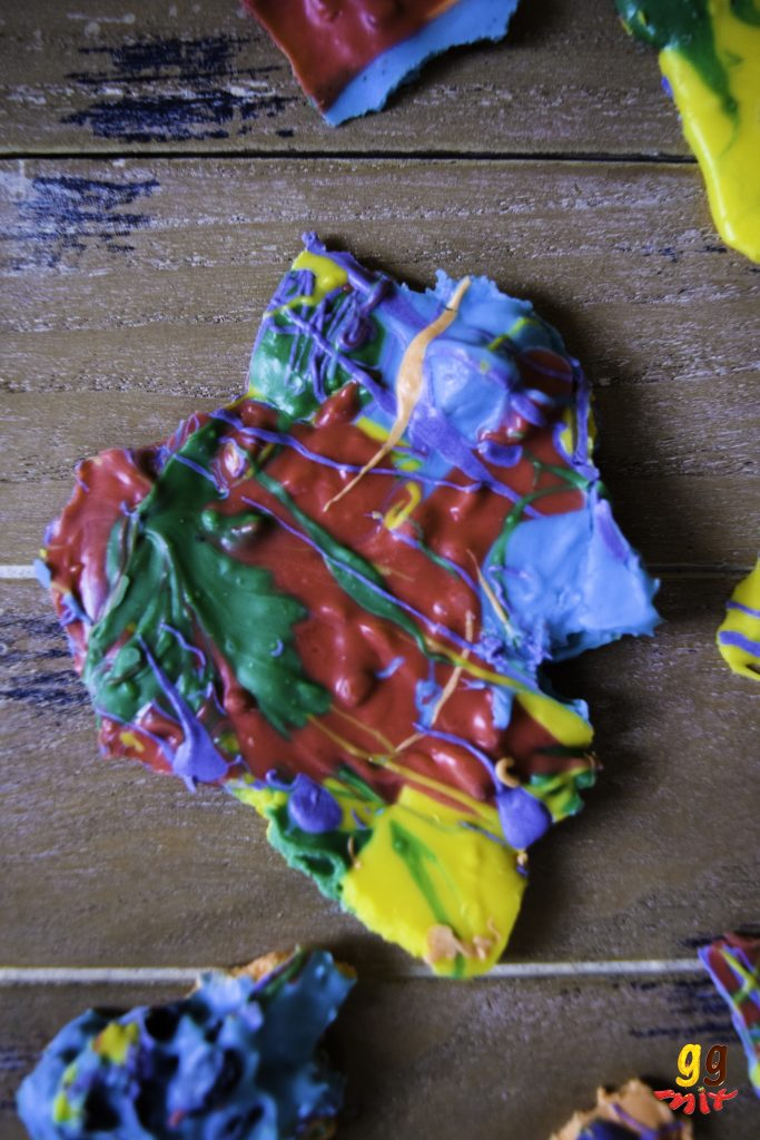 a broken piece of rainbow chocolate coloured in an abstract way with red, orange, yellow, green, blue and purple
