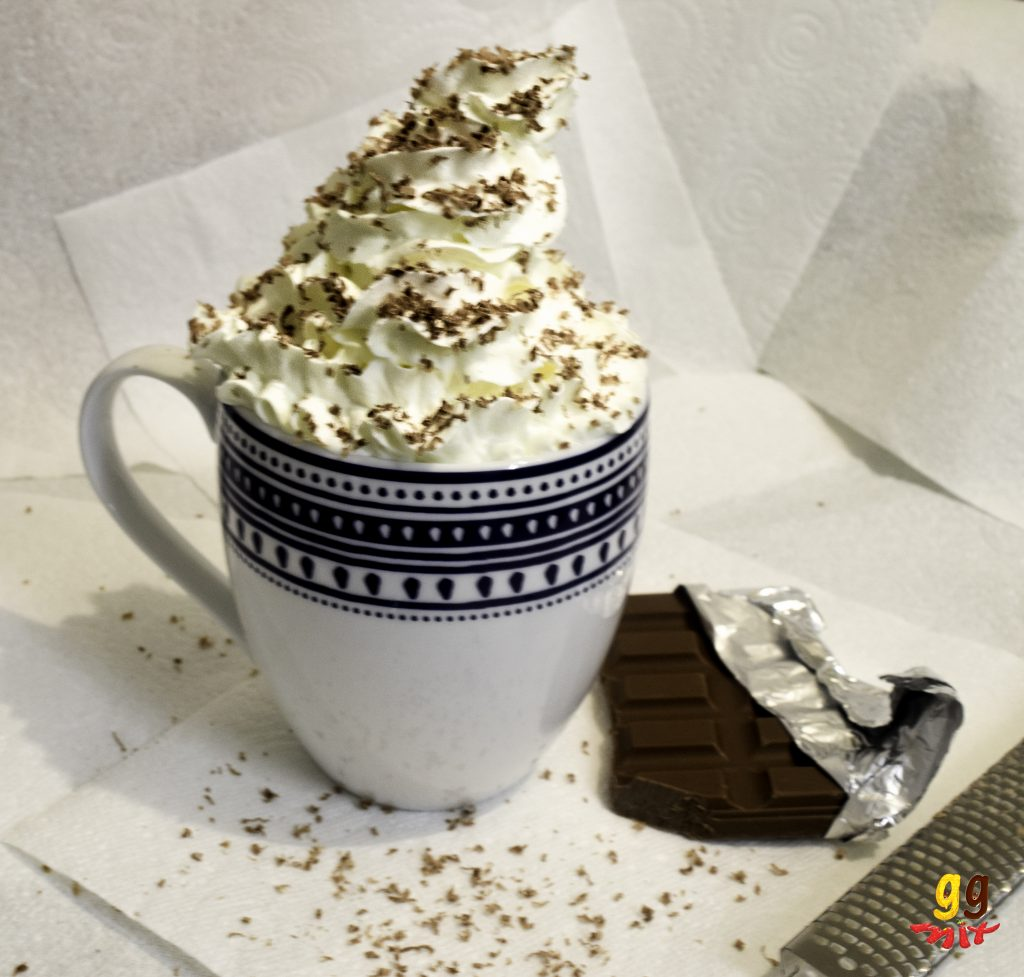 a mug of hot chocolate topped with whipped cream and chocolate shavings