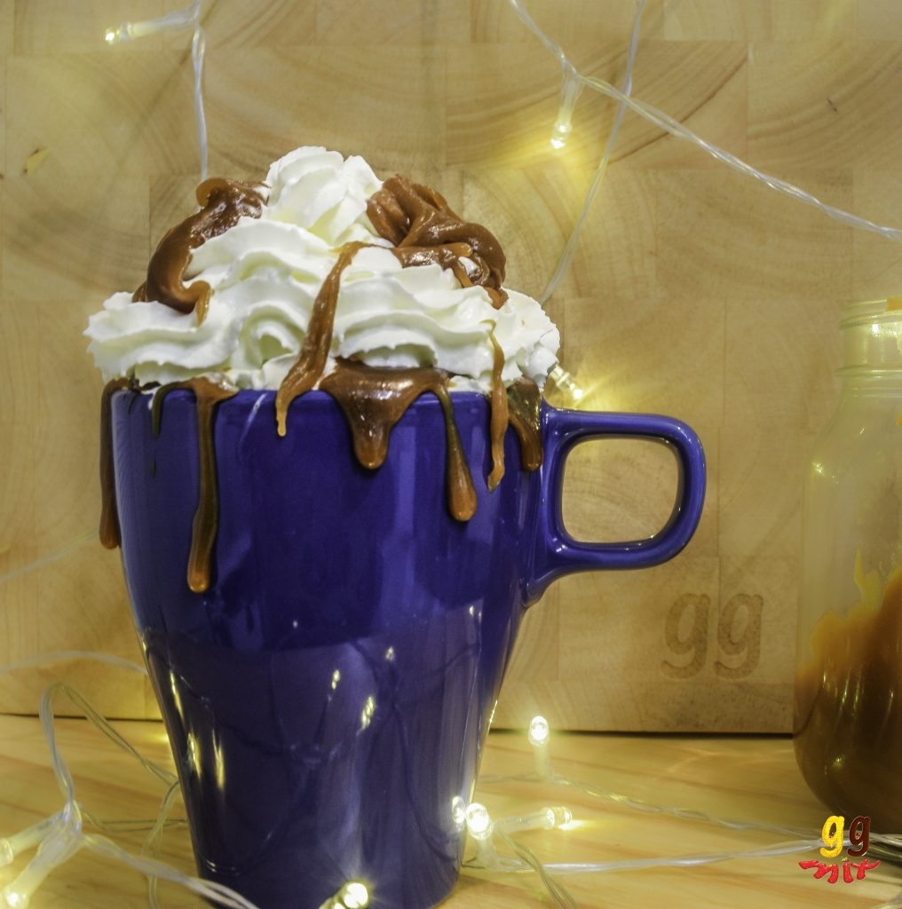 a mug of hot chocolate topped with whipped cream and salted caramel