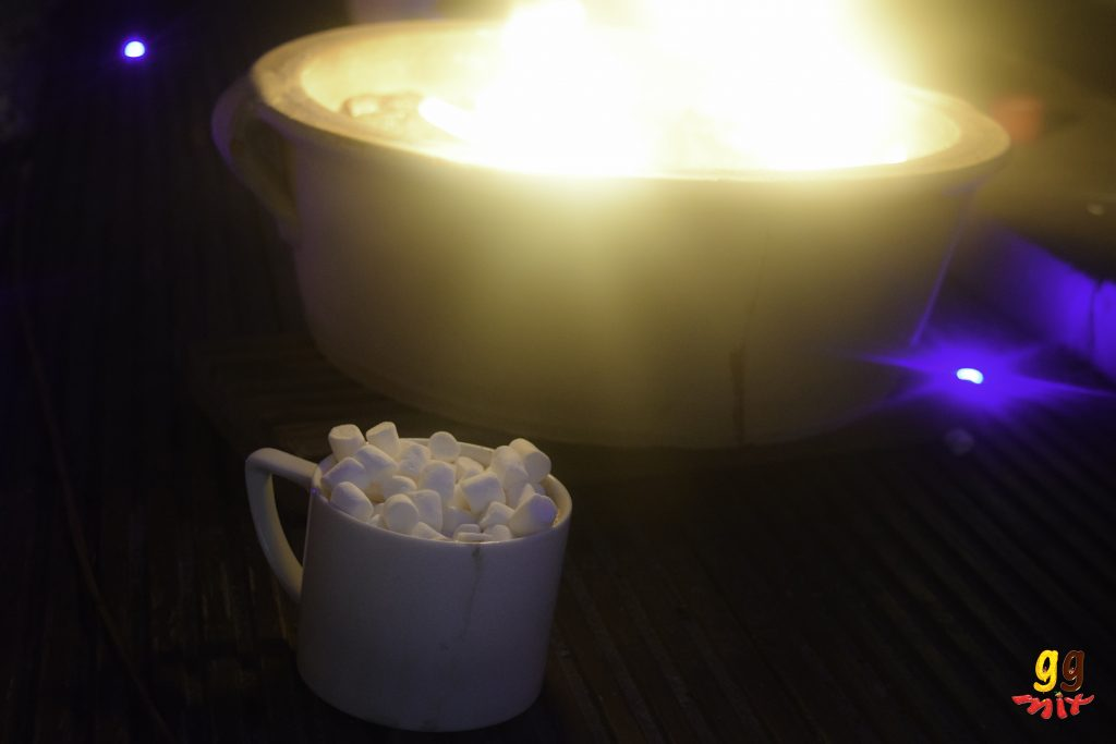 a cup of hot chocolate topped with marsmallows with a charcoal bbq burning in the background