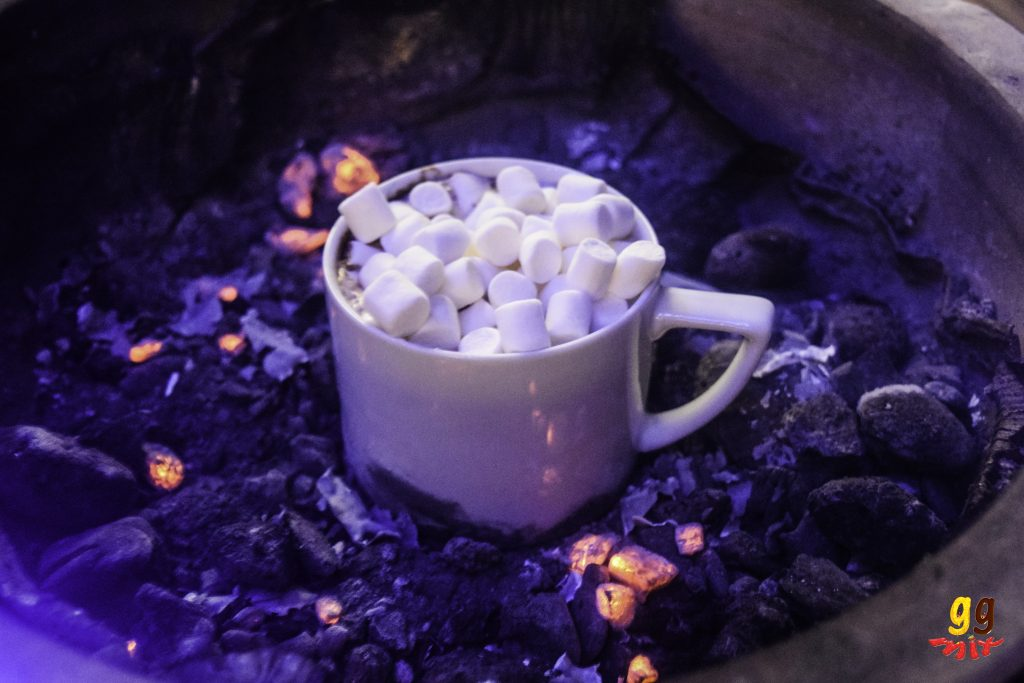 a cup of hot chocolate topped with marsmallows sitting on a charcoal bbq