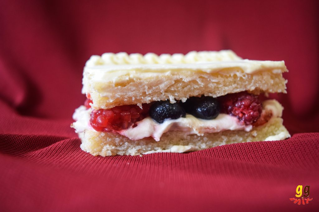 a slice of vanilla cake covered with fresh cream and filled with strawberry jam, blueberries, raspberries and fresh cream