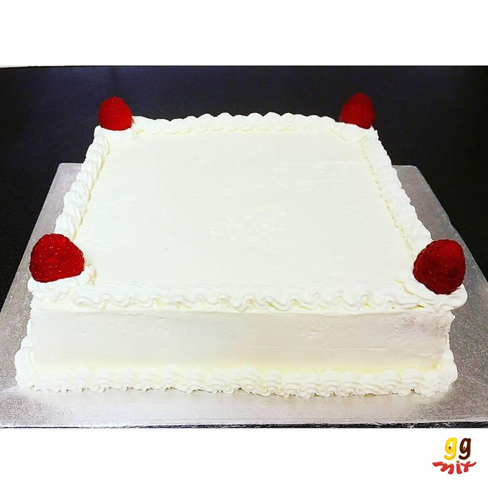 a square fresh cream cake topped with fresh raspberries