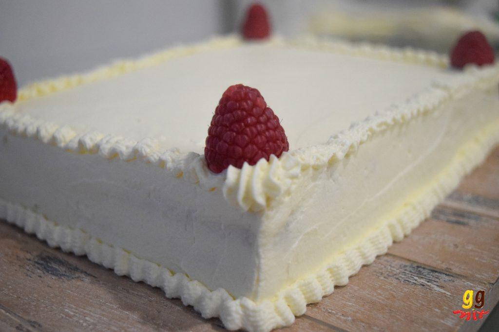 a rectangular sheet cake covered with fresh cream and raspberries