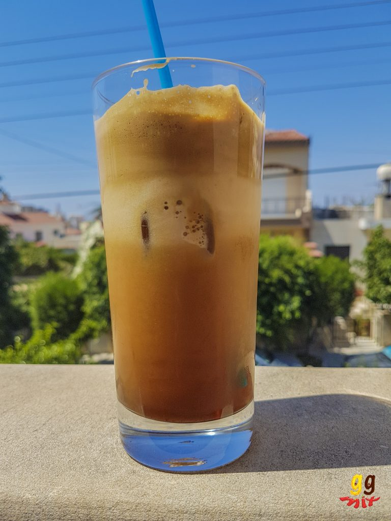 a glass of greek frappe iced coffee with a blue straw sitting in the sun