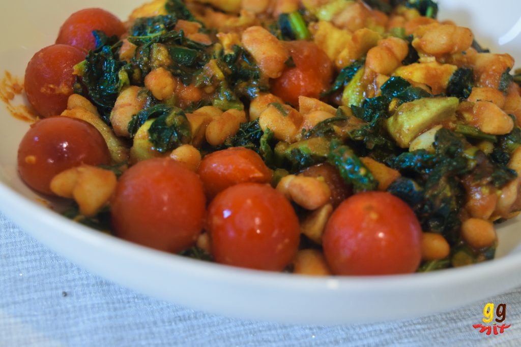 10 minute warm cannellini bean salad with caramalised cherry tomatoes, crispy cavelo nero kale, cannellini beans, chopped avocado, smoked paprika and cayenne pepper in a bowl