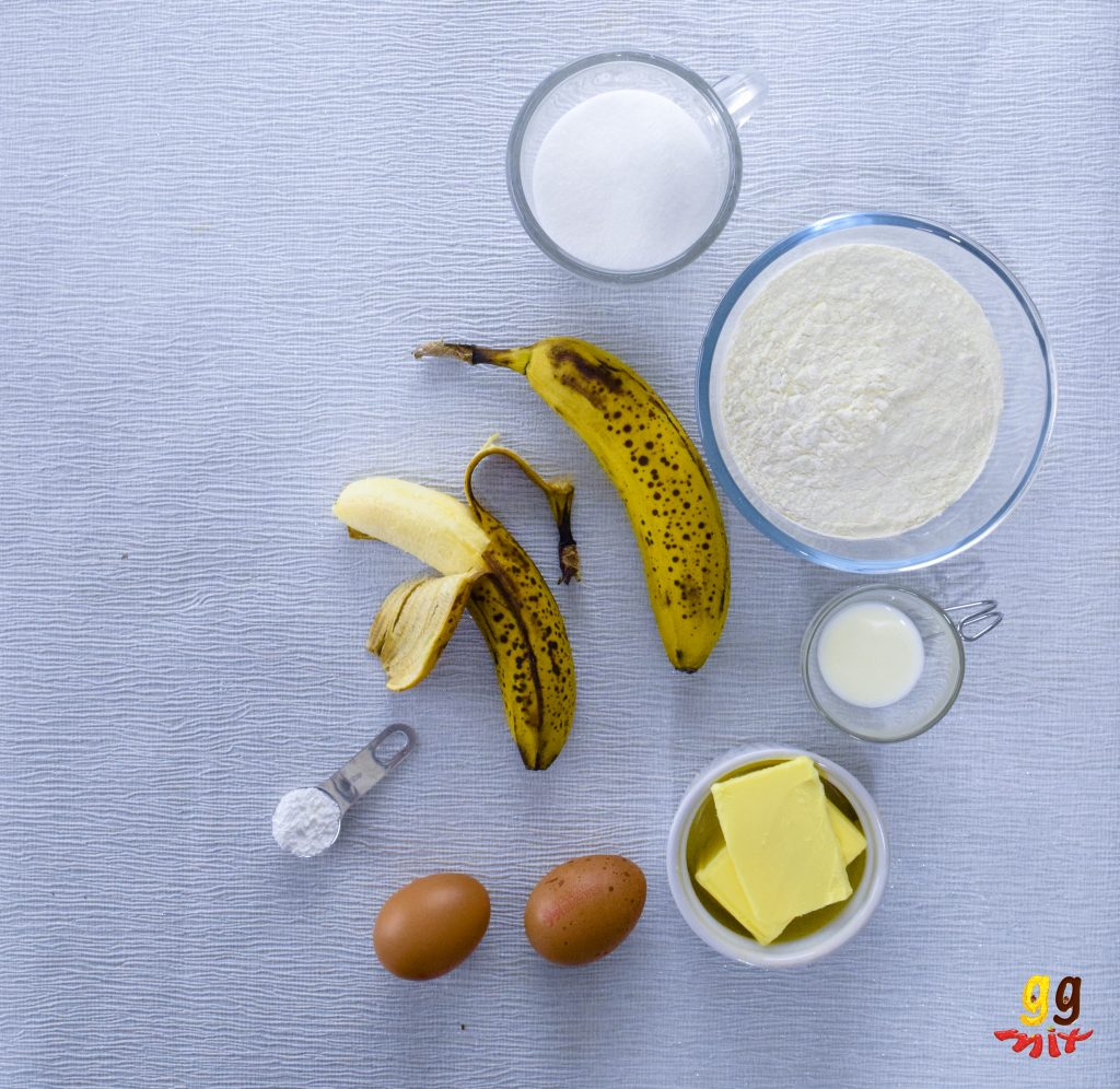 two ripe bananas yellw with brown spots , 1 banana peeled, a cup of caster sugar, a bowl of self raising flour, a cup of milk, a bowl of butter, 2 eggs in their shell a teaspoon filled with baking powder