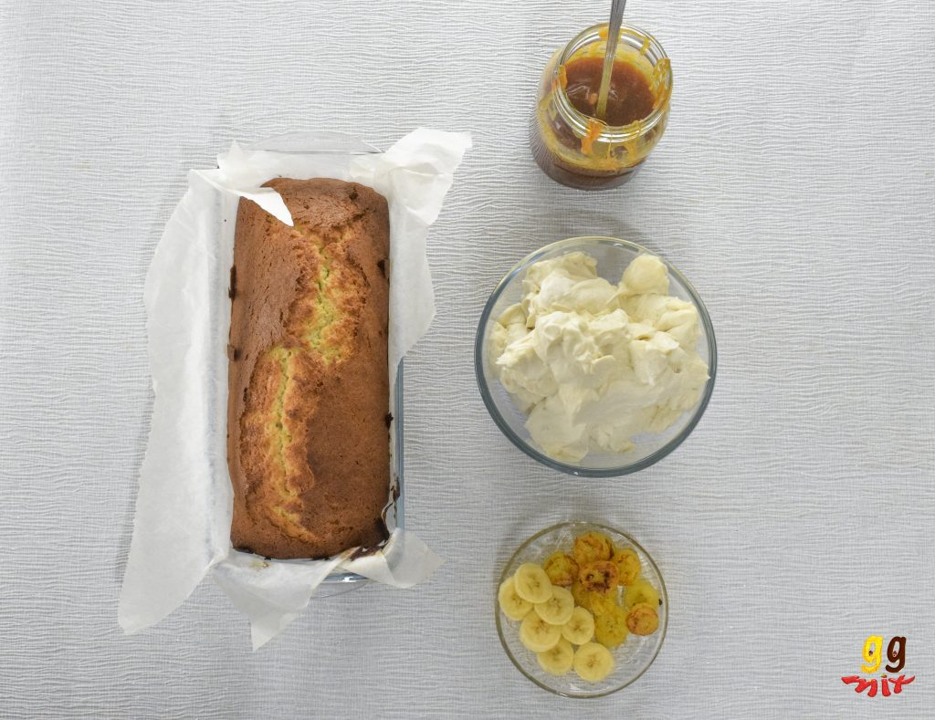 view of a banana loaf cake a jar of salted caramel, a bowl of golden cream cheese frosting and a plate of fresh and caramelised banana slices from above