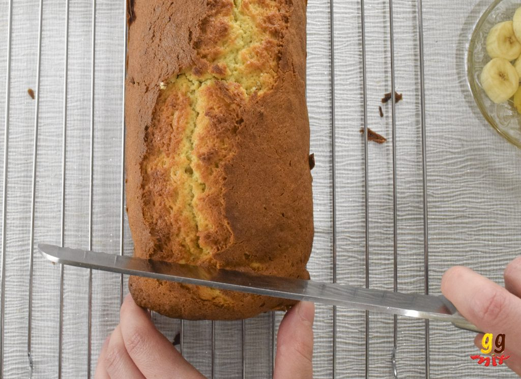 a banana loaf cake on a wire cooling rack being sliced with a bread knife