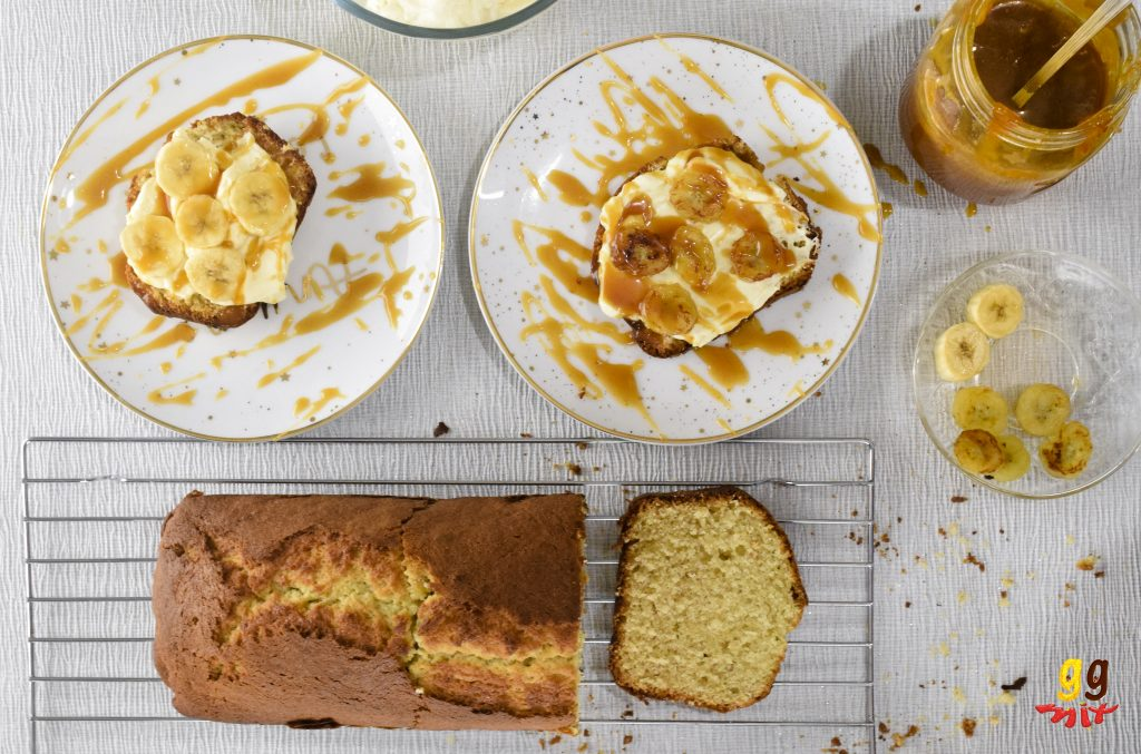 a slice of banana loaf cake on a wire rack 3 slices of bananan loaf cake one plain, two topped with a golden cream cheese frosting,, drizzles of salted caramel and fresh banana and caramelised slices , a jar of salted caramel and a plate of fresh and caramelised banana coins