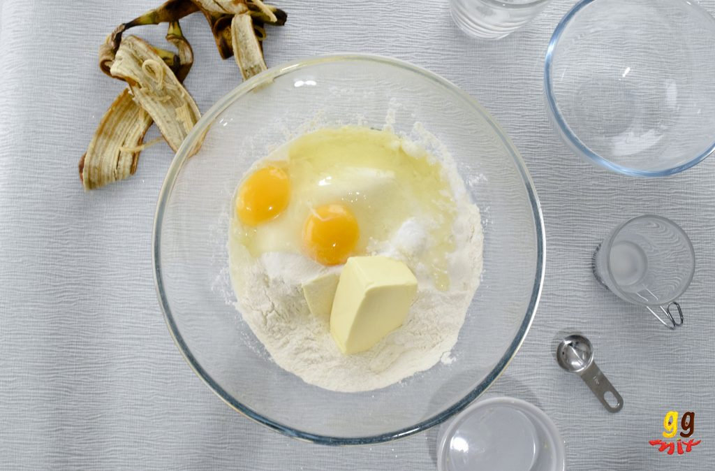 a glass bowl of self raising flour, butter, 2 eggs, 2 yellow egg yolks, sugar and baking powder, 2 ripe banana skin peels , 2 wmpty bowls an empty glass cup and a silver measuring teaspoom