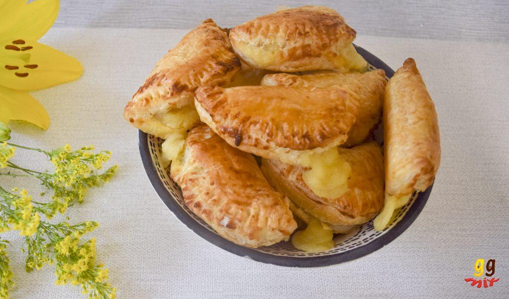 A bowl full of Bougatsa puff pastry hand pie filled with Greek semolina custard