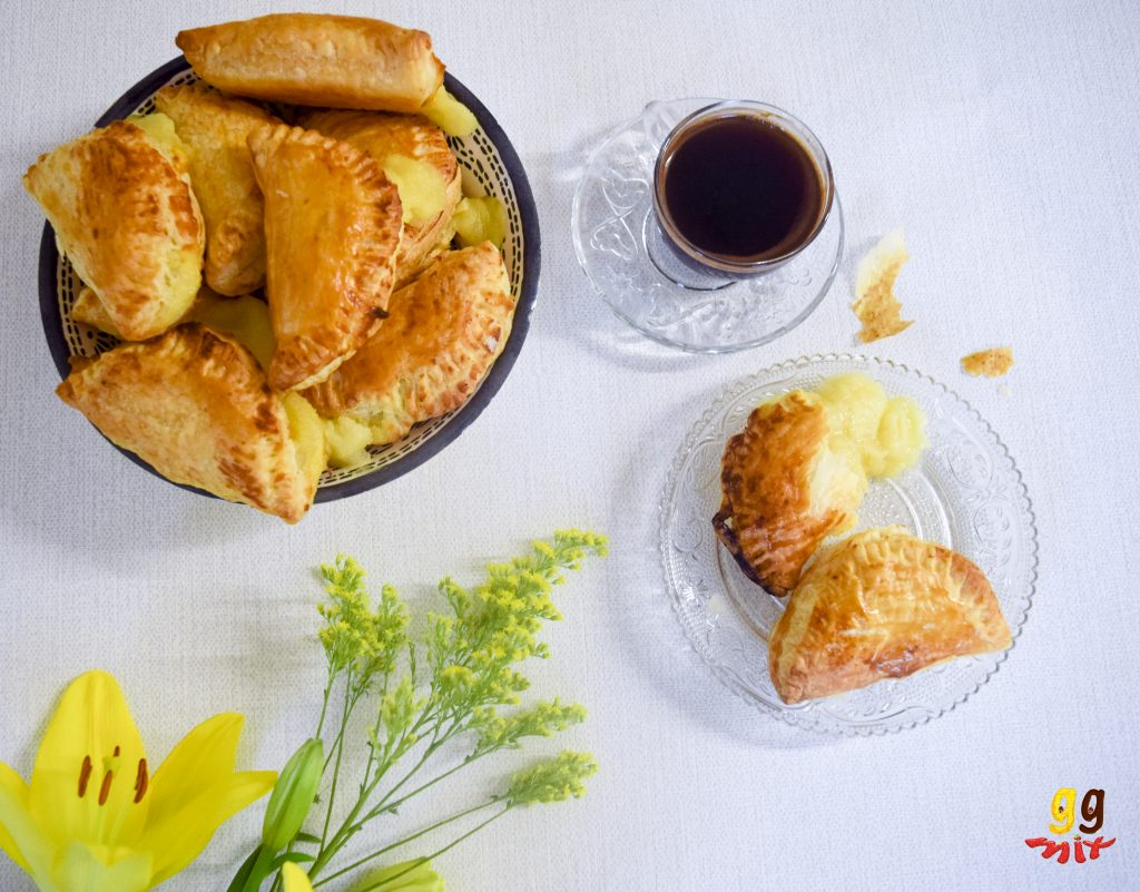 A bowl and plate full of Bougatsa puff pastry hand pie filled with Greek semolina custard and a cup of Greek coffee