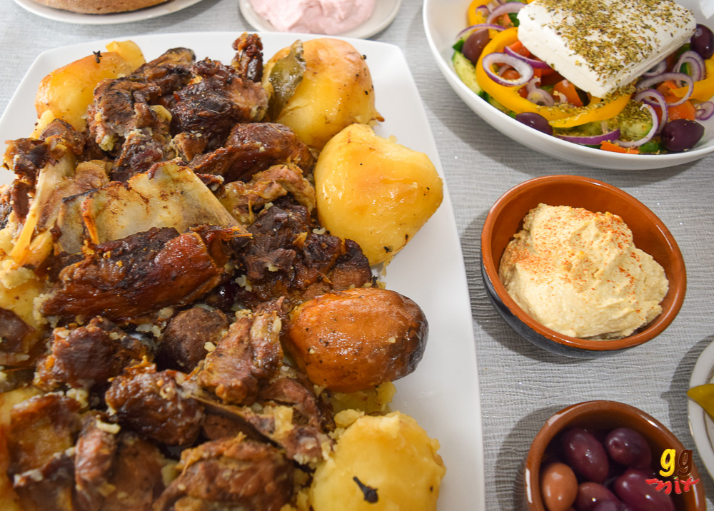 kleftiko slow cooked lamb and potatoes on a white platter, a bowl of kalamata olives, a bowl of houmous and a bowl of Greek salad