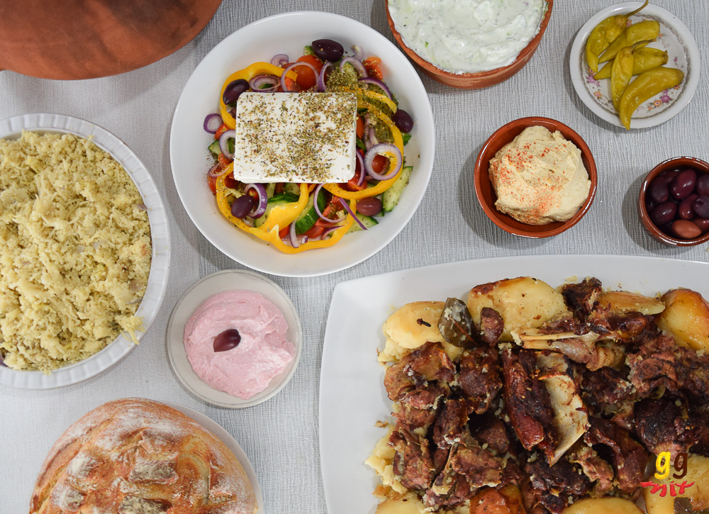 kleftiko slow cooked lamb and potatoes on a white platter, a bowl of taramasalata, a bowl of houmous and a bowl of Greek salad, pourgouri,chillies, kalamata olives, tzatziki and Greek sour dough bread