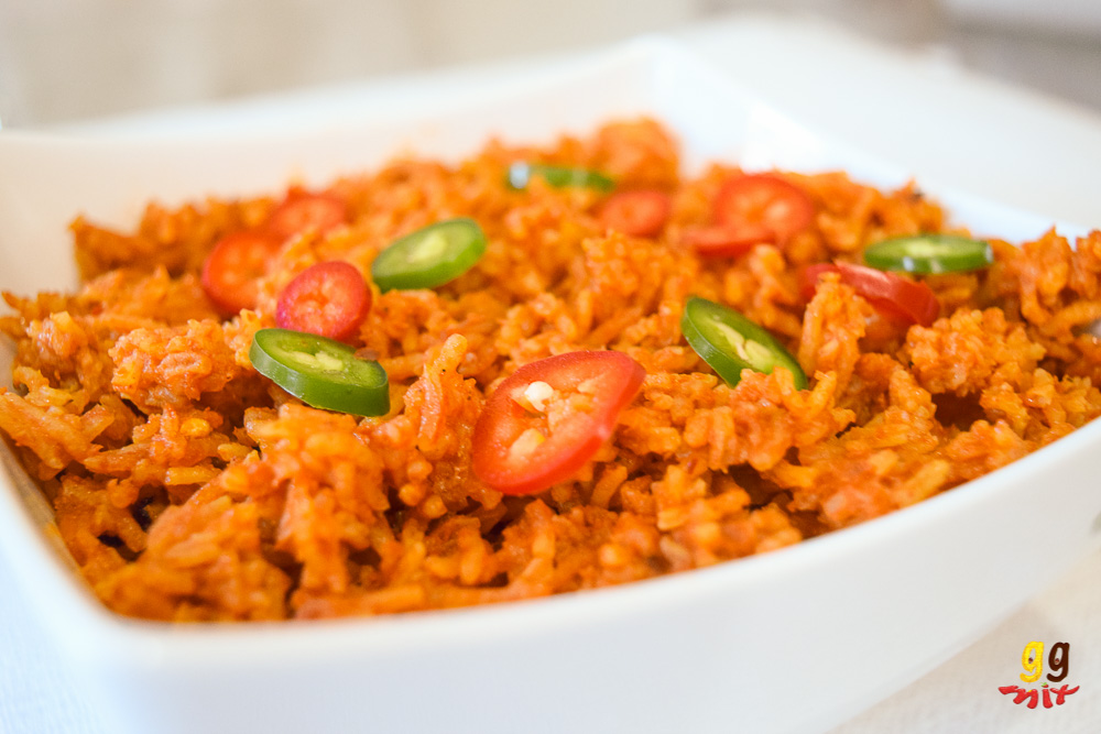 ghanaian jollof rice in a bowl with sliced red and green chillies sprinkled on the top